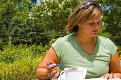 Study Lunch Outdoors - 3. Woman enjoying lunch outdoors while studying Royalty Free Stock Photography