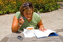 Study Lunch Outdoors - 5. Woman enjoying lunch outdoors while studying royalty free stock photos