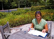 Study Lunch Outdoors - 6. Woman enjoying lunch outdoors while studying Stock Image