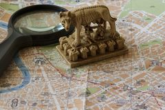 We study the map of Rome. The souvenir in the form of a feeding she-wolf is a symbol of Rome. Royalty Free Stock Image