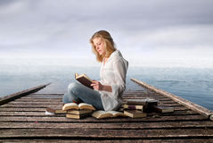 Study in nature. Portrait of a student sitting on a dock in front of the sea and reading a book royalty free stock photos