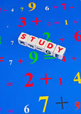 Study numbers. Text ' study ' in red uppercase letters on small white cubes with a background of numbers and signs Royalty Free Stock Photos