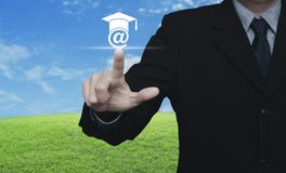 Study online concept. Businessman pressing e-learning icon over green grass field with blue sky, Study online concept Royalty Free Stock Photo