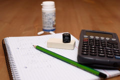 Study place with calculator and painkillers in background Stock Image