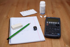 Study place with calculator and painkillers in background Royalty Free Stock Photo