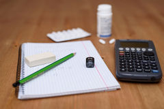 Study place with calculator and painkillers in background Royalty Free Stock Images