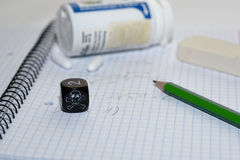Study place with painkillers in background and skull dice Stock Photography