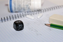Study place with painkillers in background and skull dice Royalty Free Stock Photos