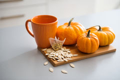 A study in pumpkin colours including a mug, seeds, and pumpkins Stock Photography