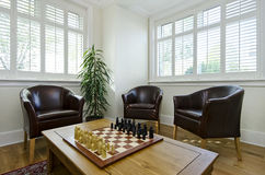 Study room with leather armchairs and chess board. Spacious and bright study room - office with three leather armchairs, wooden table and chess board set up Royalty Free Stock Image
