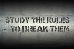 Study the rules to. Break them stencil print on the grunge white brick wall Stock Photo