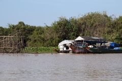 Tonle Sap lake floodplain with houseboat near a wooden fishing structure royalty free stock photo