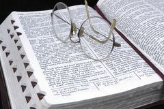 Study the Scriptures. Reading glasses on an opened set of scriptures royalty free stock image