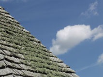 A study of a slated roof against a blue sky. Royalty Free Stock Photos