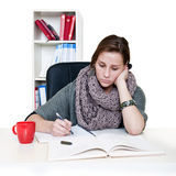 Study stare. Tired young woman staring aimlessly at her books, trying to study royalty free stock images