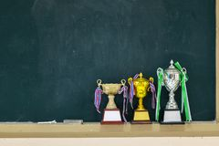 Received many trophies put on a blackboard stock image