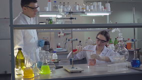 Study team working in laboratory. Adult woman scientist or doctor explain man technology carrying out experiments. Chemist engineer holding flasks adding liquid stock video footage