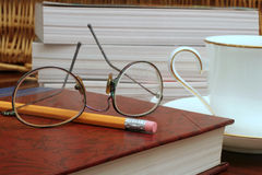 Study time. Shot of books, tea, glasses & pencil royalty free stock image