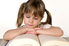 Study time. A young girl reading a book royalty free stock images
