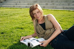 Study Time On Campus. A female student laying on campus grass with a text book open Stock Photos