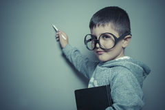 Study, young student writing on a blackboard school with a book. In hand and big glasses Stock Images