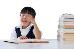 Studyin d'uso sorridente dell'uniforme scolastico della bambina cinese asiatica Immagine Stock Libera da Diritti