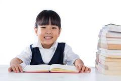 Studyin d'uso sorridente dell'uniforme scolastico della bambina cinese asiatica Immagini Stock Libere da Diritti