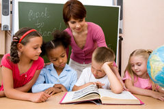 Studying. Image of group of schoolchildren and teacher reading book together in the classroom Stock Image