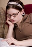 Studying. Attractive teen studying on the couch stock photography