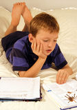Studying. Young boy doing his homework on his bed using a dictionary Stock Photography