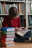 Studying. A girl sitting near the books and studying Royalty Free Stock Photos