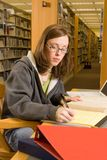 Studying. A young woman studies in the library Royalty Free Stock Images