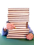 Studying. Guy holding pen and glasses behind a pile of books Royalty Free Stock Photo