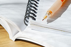 Studying. An orange mechanical pencil on top of a spiral notebook and a few books royalty free stock images