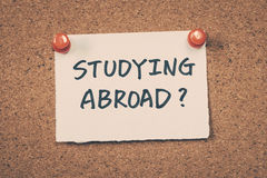 Studying abroad. Concept word text message on bulletin board Stock Images