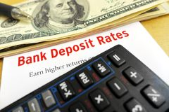 Studying bank deposit rates. A photograph showing some us dollar bank notes taken with a calculator and the words bank deposit rates in red on white.  Conceptual Stock Photos