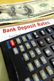 Studying bank deposit rates. A photograph showing some us dollar bank notes taken with a calculator and the words bank deposit rates in red on white.  Conceptual Stock Photo