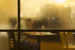 Studying Behind Dew Covered Glass. A view of cafe blurred by dew which cover the glass giving a cozy feeling. showing here is a man studying by himself Royalty Free Stock Photos
