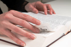 Studying The Bible. Woman's hands on a Bible, turning a page Royalty Free Stock Photography