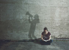 Studying the Bible in silence. Woman reading a Bible while her shadow shouts out loud stock photos