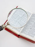 Studying the Bible using a magnifier. A copy of the New Testament is seen with a magnifying glass to assist in reading the small print stock illustration