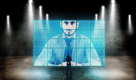 Studying a big screen. Young businessman looking at a big screen and talking to hologram Royalty Free Stock Image
