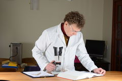 Studying Book. Scientist in white coat standing behind a microscope.  Referring to reference book Stock Photos