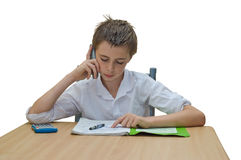 Studying boy. A teen boy studying and getting help from someone on the phone royalty free stock photos