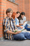 Studying boy friends sitting ground outside campus Royalty Free Stock Image