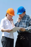 Studying building plans. Young couple wearing helmets studying building plans of their new house Stock Images