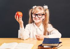 Studying in Classroom. Cute young girl wears in smart eyeglasses holding apple before dark background stock photography