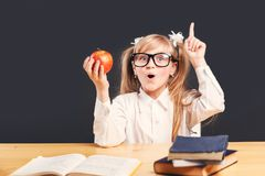 Studying in Classroom. Cute young girl wears in smart eyeglasses holds red apple has idea learning English language with book before dark background stock photos