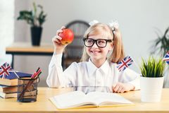 Studying in Classroom. Happy smiling girl learning English language holding red apple in light stylish classroom, studying success concept royalty free stock images