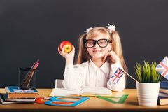 Studying in Classroom. Happy smiling girl wears in smart eyeglasses holding apple learning English language with book before dark background stock image